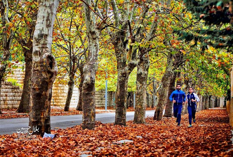 A couple jog on a street covered with fallen leaves in Sawfar village,...