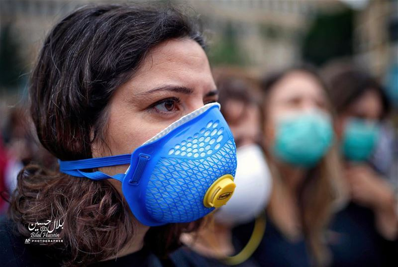 A Lebanese anti-government protester wears a surgical mask during a...