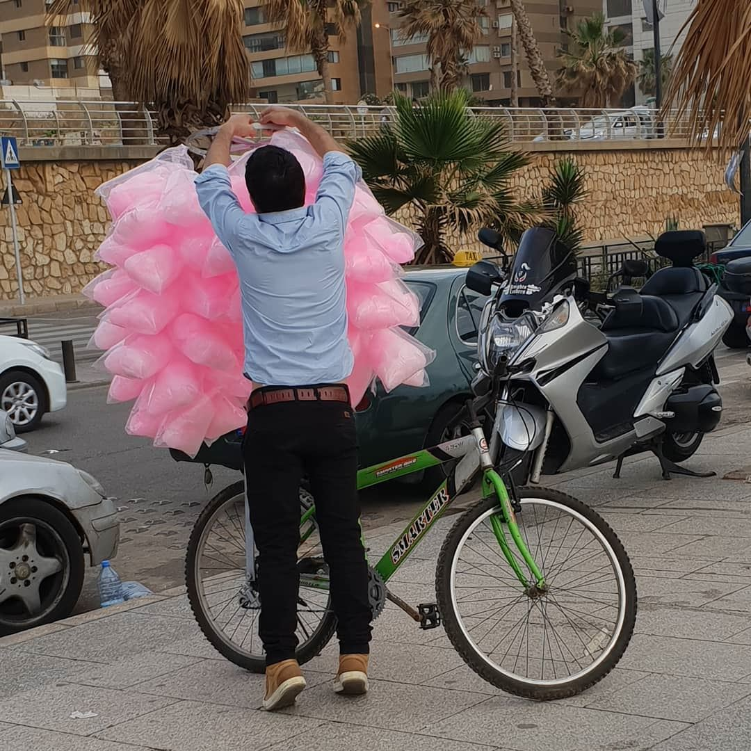 Cotton Candy boy with his green bike. Making summer in Beirut more joyful.... (Ramlat Al Bayda', Beyrouth, Lebanon)