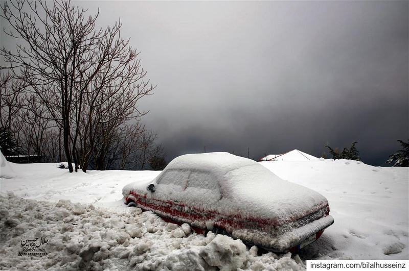 A car is covered with snow during a heavy snowfall in the village of...