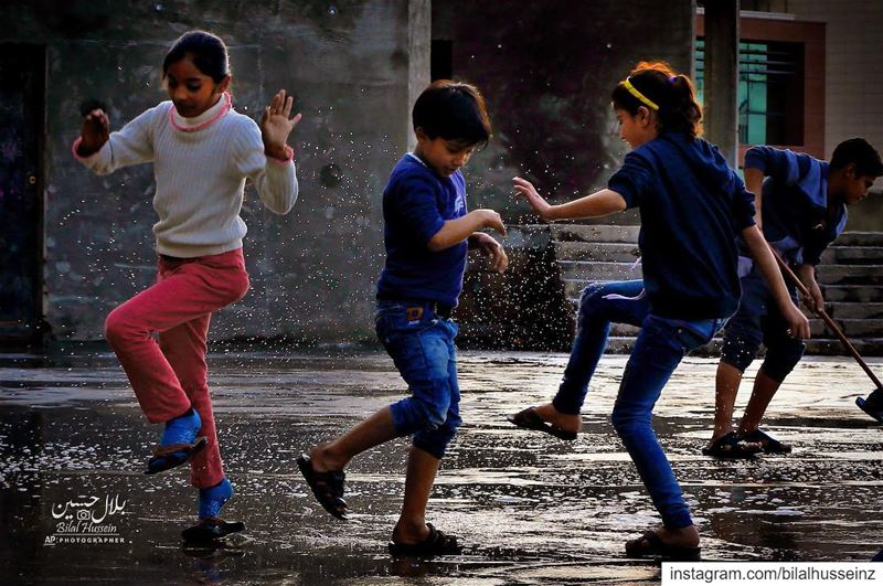Syrian refugee children play in rain water in a refugee settlement in...