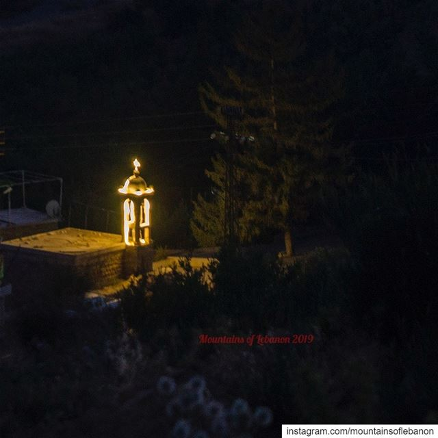 in the dark night, an illuminated small church bell tower, next to a fir... (Afka, Mont-Liban, Lebanon)