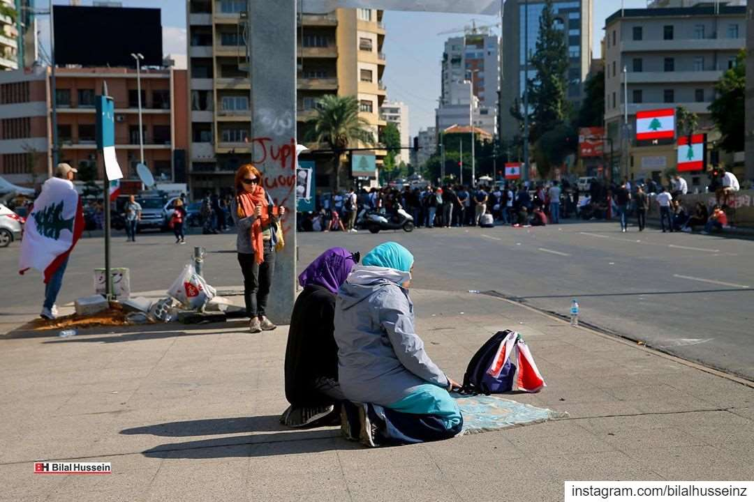 Anti-government protesters pray, as others block a main highway in Beirut,...