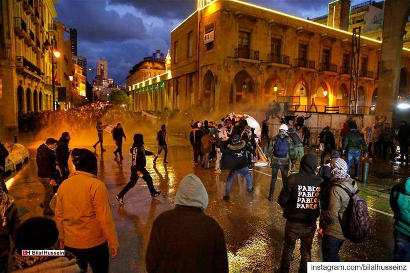 Anti-government protesters are sprayed by a water cannon as they throw...