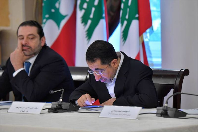 PM Saad Hariri taking a glance toward minister Hussein Hajj Hassan, as he looks busy working on his mobile phone, inside the grand Serail in Beirut, Lebanon. (Nabil Ismail)