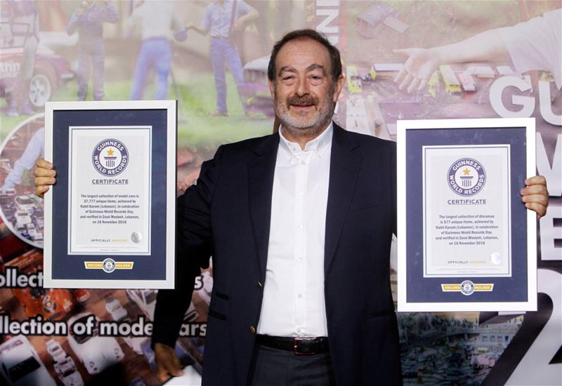Nabil Karam poses with his Guinness World Record certificates for the largest collection of model cars and the largest collection of dioramas, in Zouk Mosbeh.
