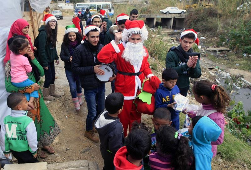 Students at the Evangelical School for Arts distribute Christmas gifts to Syrian refugees in Saida.