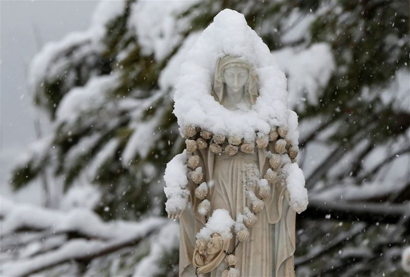 Snow covering a statue of the Virgin Mary in Bikfaya