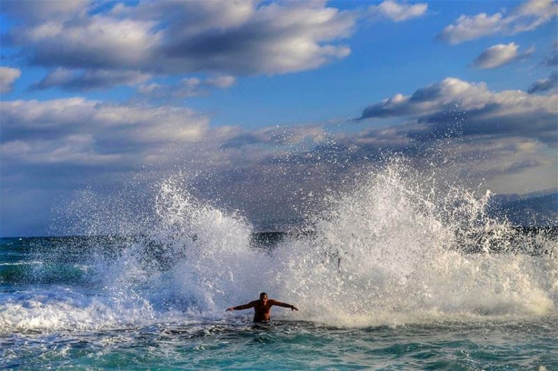 Despite the cold weather, a man is hit by waves during an early morning swim in Beirut. (Hassan Ammar)