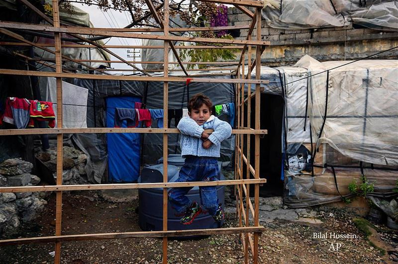 A Syrian refugee boy plays outside his family tent, at a Syrian refugee...