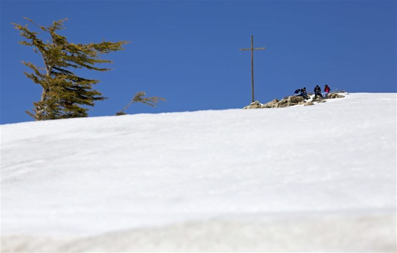People pray next to a cross on the top of a mountain at the Faraya-Mzaar ski resort. (Hassan Ammar / AP) via pow.photos