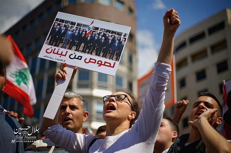 A Lebanese anti-government demonstrator holds a sign with a photo of the...