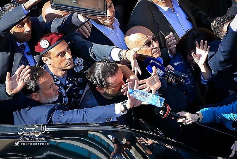 Bodyguards protect Lebanese Prime Minister Saad Hariri, center, from a...