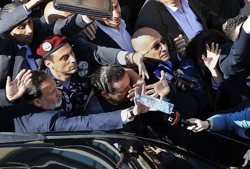 Bodyguards protect Saad Hariri, from a water bottle thrown by demonstrators in downtown Beirut. (Bilal Hussein / AP) via pow.photos