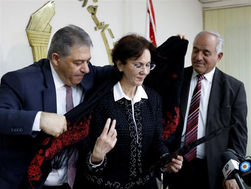 Palestinian Ambassador Ashraf Dabbour (L) helps ESCWA Executive Secretary Rima Khalaf (C) put on a traditional Palestinian scarf after announcing her resignation from her position, in Beirut. (Jamal Saidi / REUTERS) via pow.photos