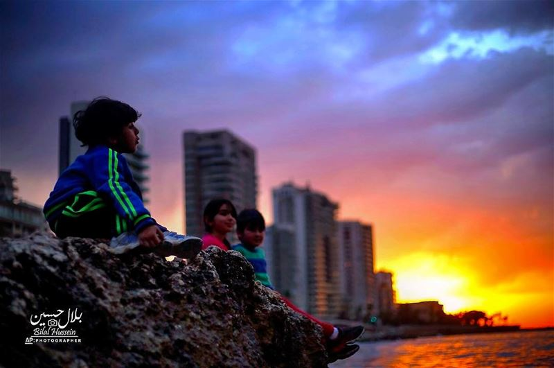 Children sit on a rocky area along the coastline as the sunset over the...