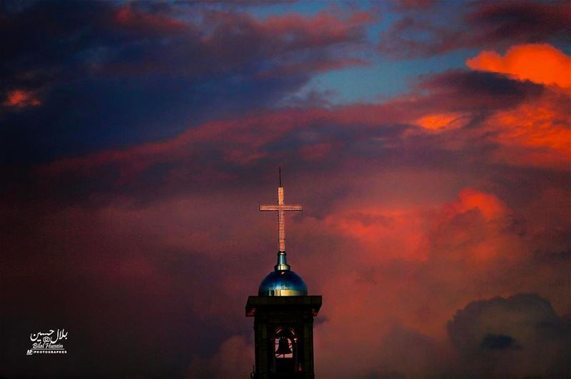 Saint George Maronite Cathedral's cross is lit while heavy clouds darken...