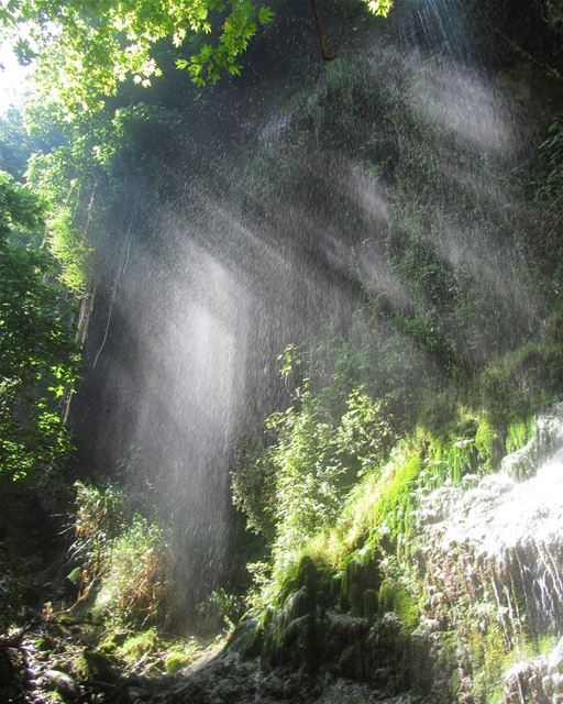 A waterfall looking like a curtain with the sun rays cutting through it ...