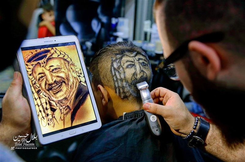 Muhannad Khaled Omar, shaves an image of the late Palestinian leader...