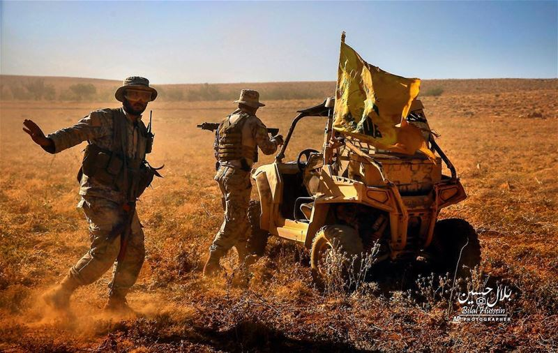 Hezbollah fighters stand near a four-wheel motorcycle positioned at the...