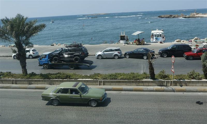 Passing by younger car being carried, while driving an old one along the... (Tripoli, Lebanon)