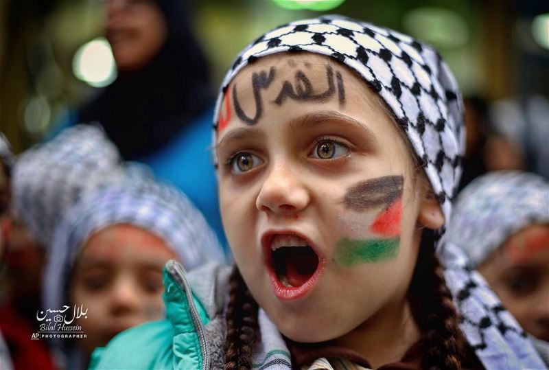 "A girl with a Palestinian flag and Arabic that read ""Jerusalem is for us""..."