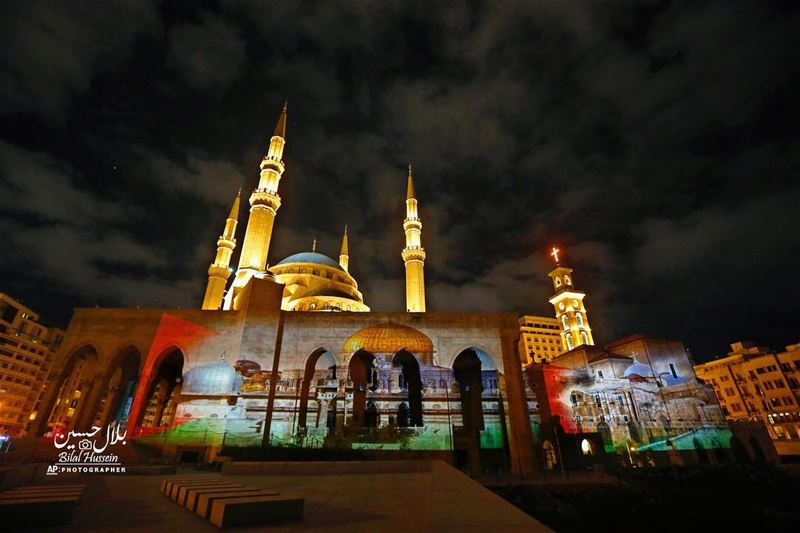 The Muhammad al-Amin Mosque, right, illuminated by a giant poster of the...