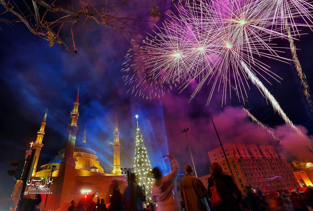 Fireworks go off near a giant Christmas tree, set in front of Muhammad al-A