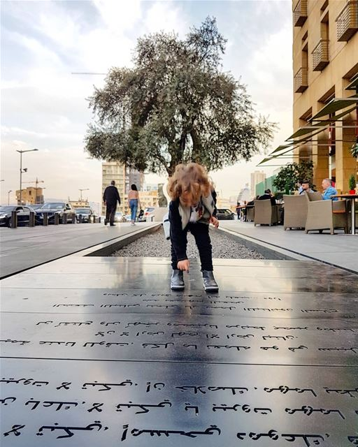 Happy boy jumps on poetic writings in downtown  Beirut by journalist ... (Le Gray, Beirut)