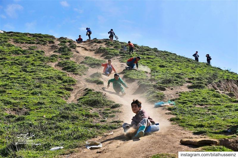 Displaced Syrian children slide down a hill, above a refugee camp in the...