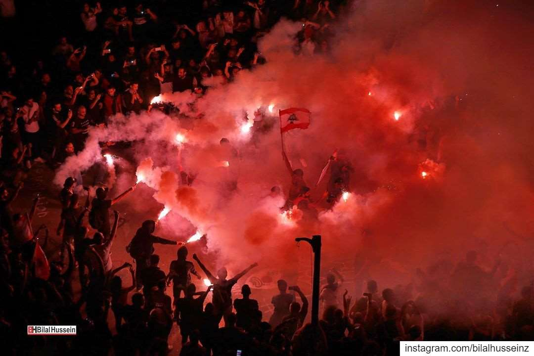 Anti-government protesters light flares and chant slogans against the...