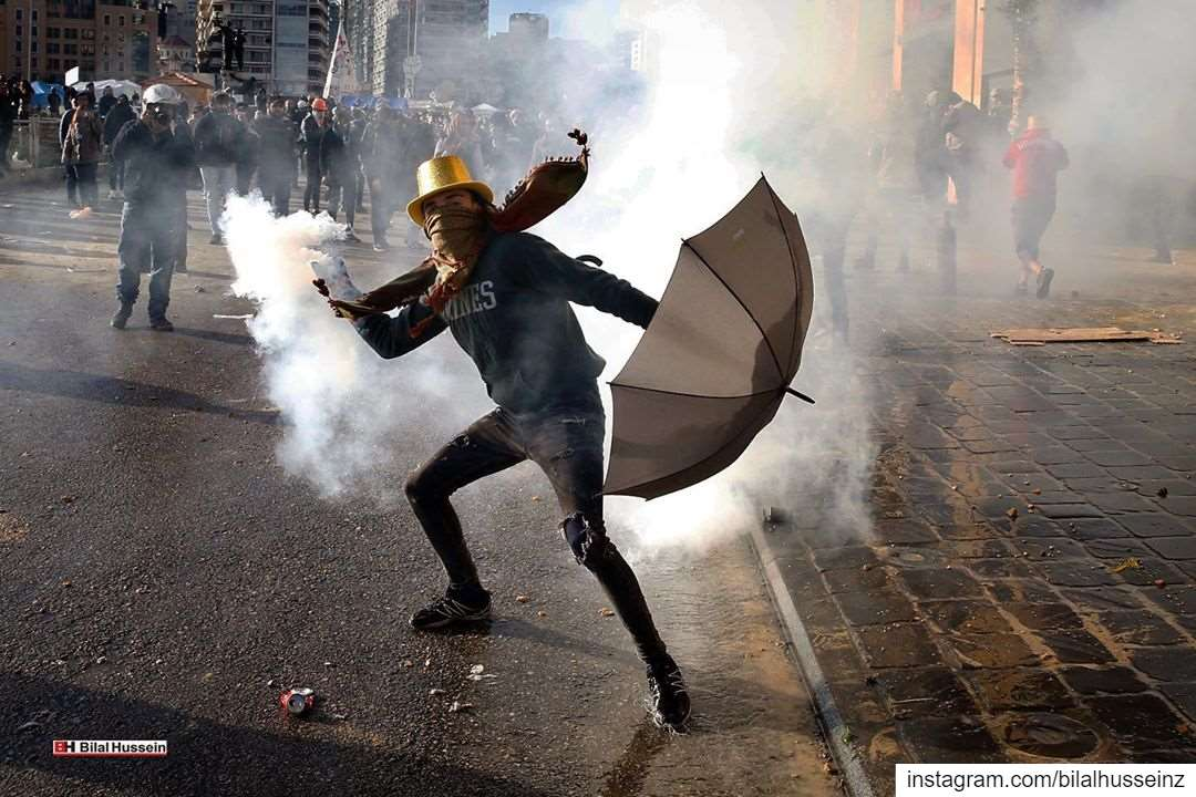 An anti-government demonstrator throws back a tear gas canister towards...