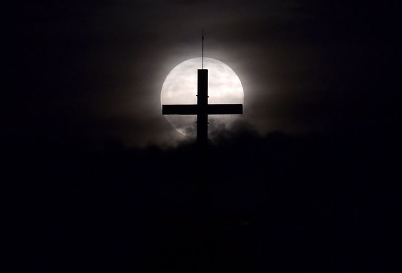 The supermoon rises behind a cross at downtown Beirut.