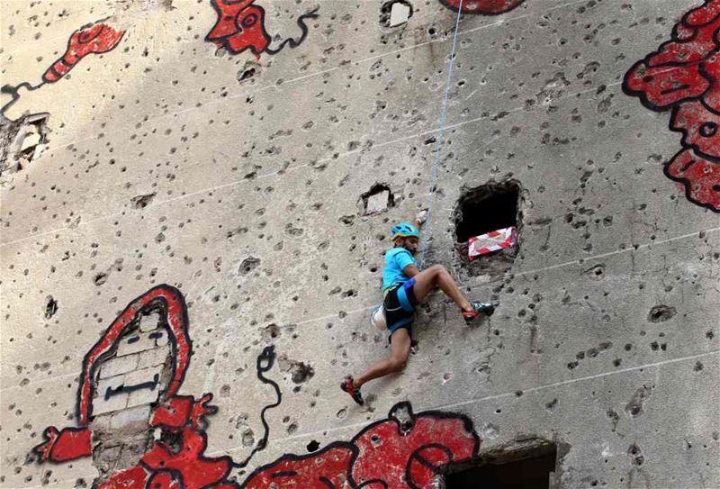 A competitor climbing the hole-ridden facade of Beirut's al-Kamal building, during an urban climbing contest.