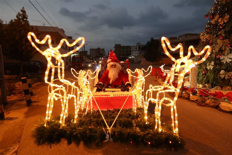 Santa Claus rides a Christmas decorated vehicle in Jiyeh.