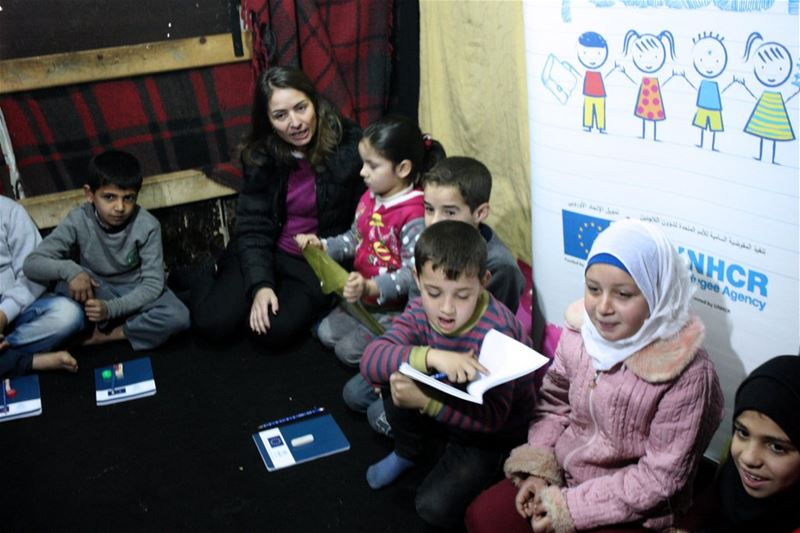 Syrian refugee children sit outside their makeshift home in a slum in Dbayeh.