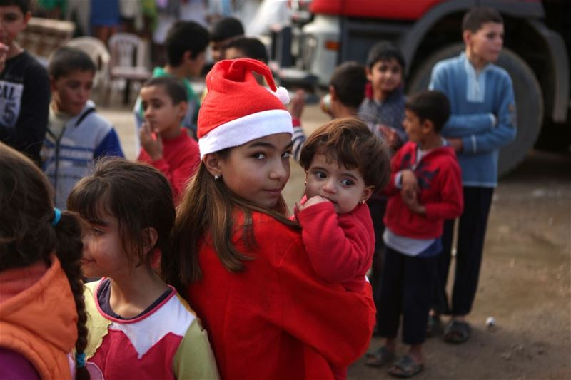 "Chloe, holds a Syrian refugee during a gift distribution by the ""Mission de Vie"" in a slum in the town of Dbayeh. (PATRICK BAZ / AFP)"