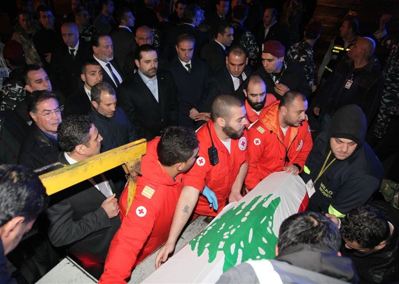 Saad Hariri looking at coffins of three Lebanese who were killed in the Reina shooting as they are being repatriated at Beirut airport.