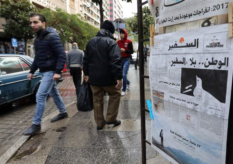 People walk past a newspaper stand, displaying the last issue of As-Safir newspaper, in Beirut's Hamra neighborhood. (ANWAR AMRO/ AFP)