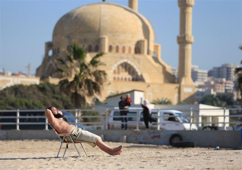 A man sunbathes at a beach in Sidon. (Ali Hashisho / REUTERS)