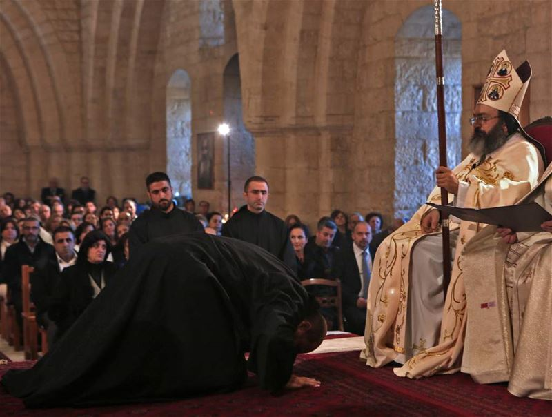 Christian monk kneels in front of his Bishop during an ordination ceremony held at the monastery of Saint Anthony in Ghazir north of Beirut. (PATRICK BAZ / AFP)