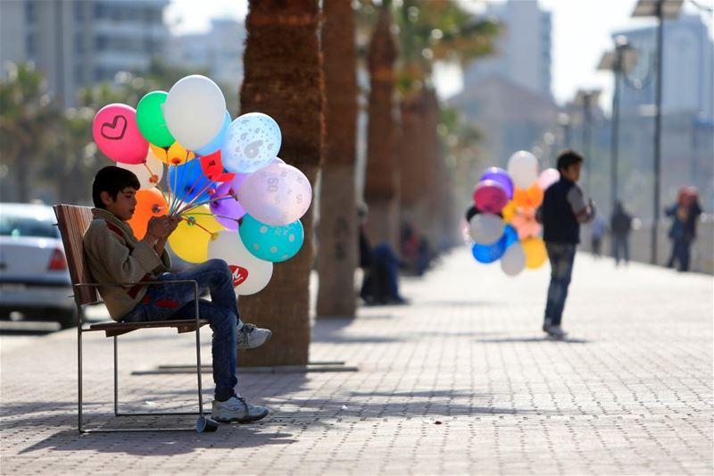 Syrian boys selling balloons along a corniche in Saida, South Lebanon