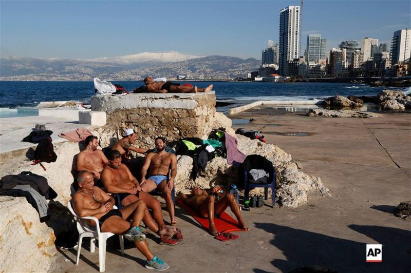 Men sunbathing by the Mediterranean sea, as snow is seen on the background covering the mountains, in Beirut, Lebanon