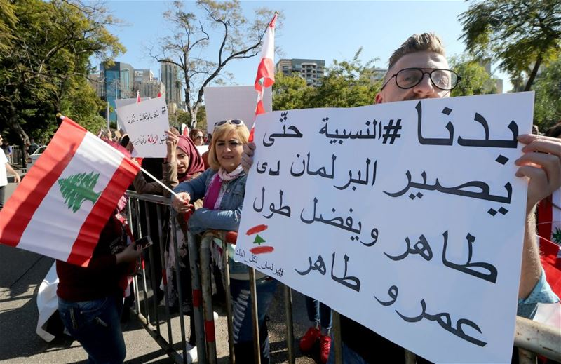 Lebanese demonstrators carry placards reading 'We need an election at proportion law', in Beirut. (NABIL MOUNZER / EPA)