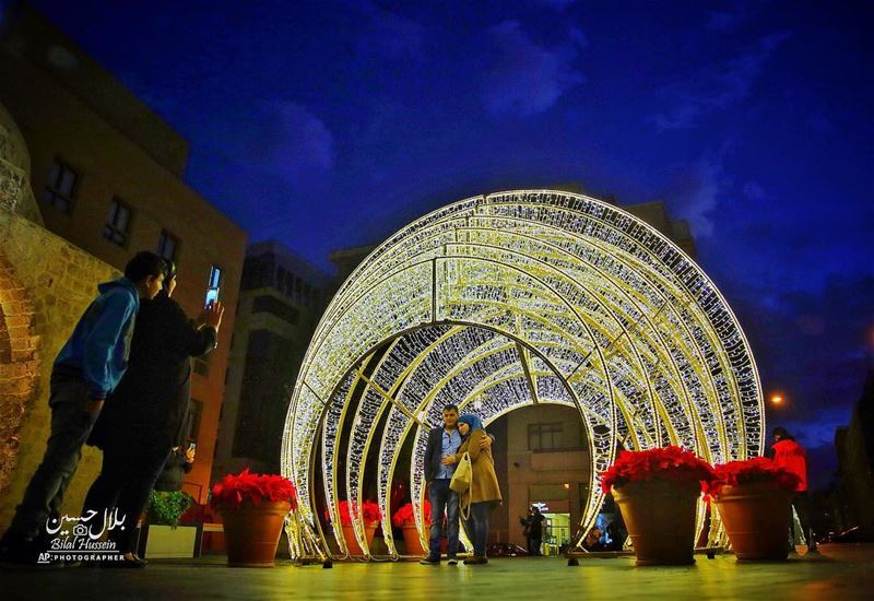 Two people take a photo of a couple near Christmas decorations in downtown...