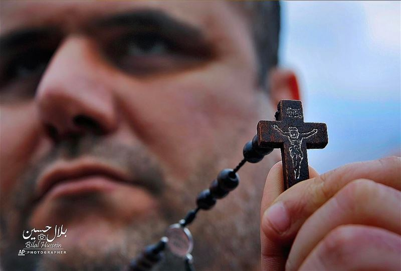 Iraqi Christian Samer Younan who lives in Lebanon holds a cross during a...