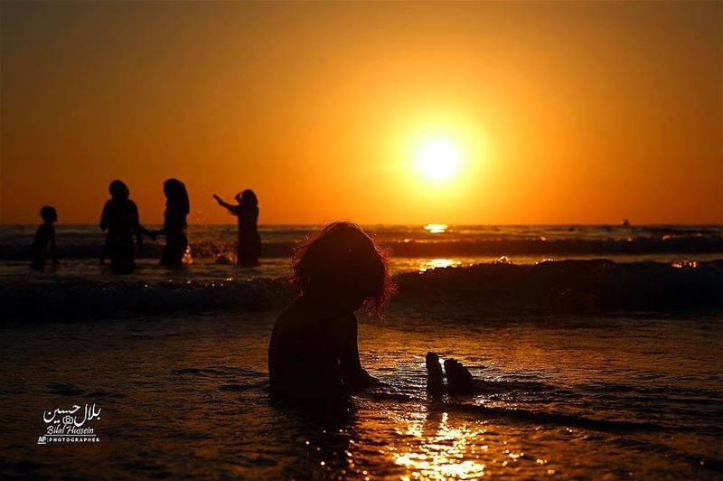 An Iraqi family swims as they spend a day while the sun sets over the...