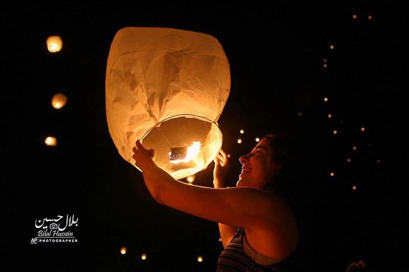 A Lebanese woman releases a paper lantern during Lebanon Lantern Festival...