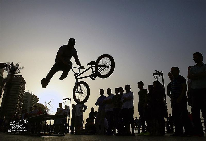 A crowd watches Walid Kasim, 23, a Turkish cyclist living in Lebanon, as...