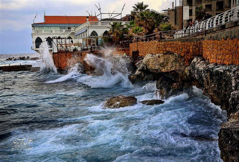 Lebanese stand on the Corniche as they look to high waves crash on the...